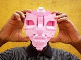 upclose shot of black man's hands holding a pink lego mask