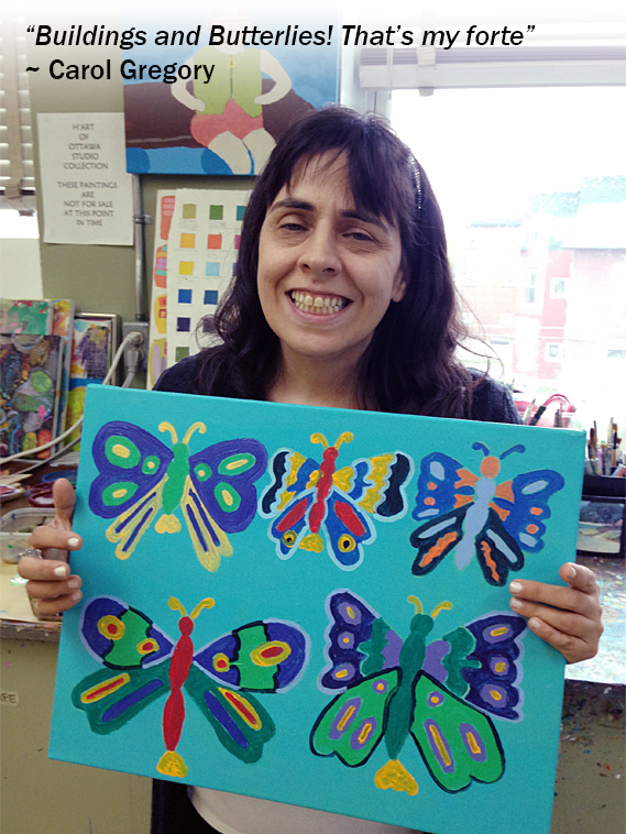 Image of woman holding a colourful painting of butterflies