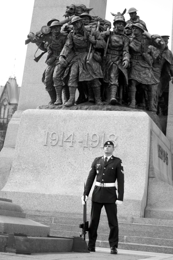 Soldier standing on guard in front of monument for World War One
