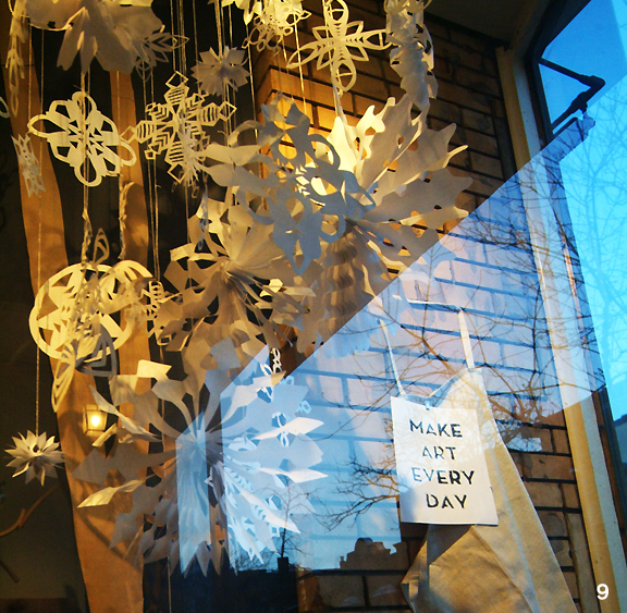 Window display with paper snowflakes and a poster that says Make Art Everyday