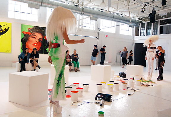 Female artist painting model in suit and large wig. Crowd watchs.