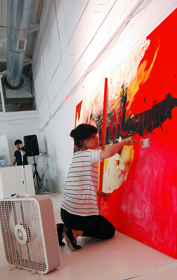 Woman painting a large canvas with broad brush strokes. DJ spinning records in the background.