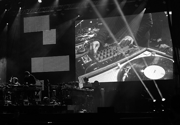 Large screen on stage with hands of DJ spinning records and performing