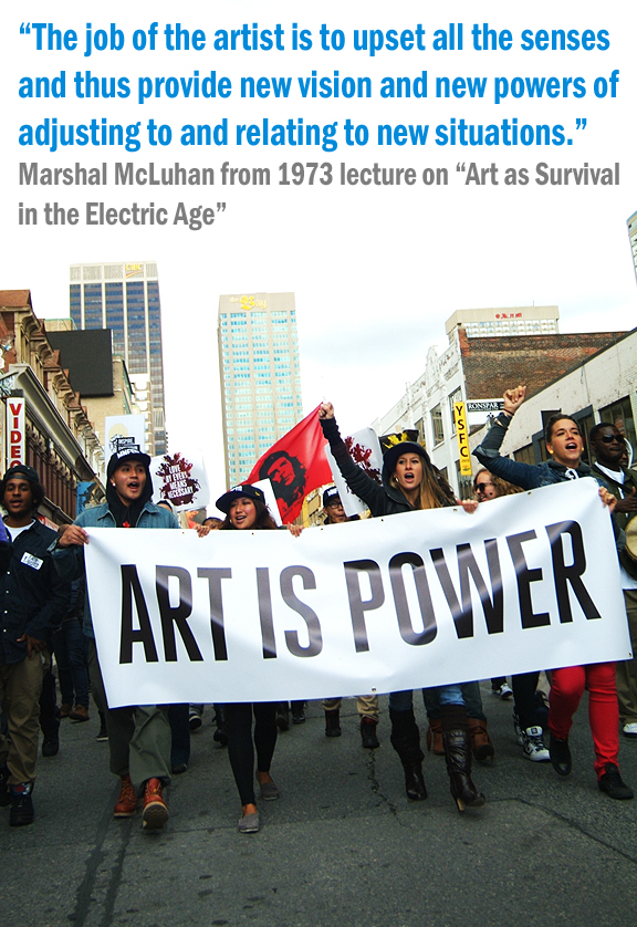 Multi-racial group of young people walking in middle of street holding up white banner that reads Art is Power