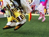 The feet of indigenous dancers performing, both male and female, beadwork on their moccasins