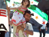 Syrian girl on the shoulders of her father holding a Syrian flag