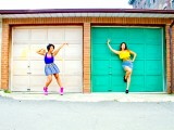 Two dancers posing in front of garage doors