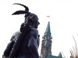 Statue of Aboriginal man in traditional dress with Canada's Parliament Building in the background