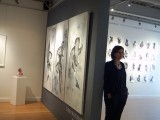 Middle eastern woman standing against a wall in a gallery with her artwork behind her
