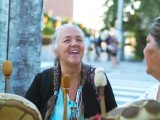 Woman smiling in group of women playing traditional indigenous hand drums on street corner
