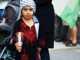 Small Palestinian girl dressed in traditional clothes and holding a candle
