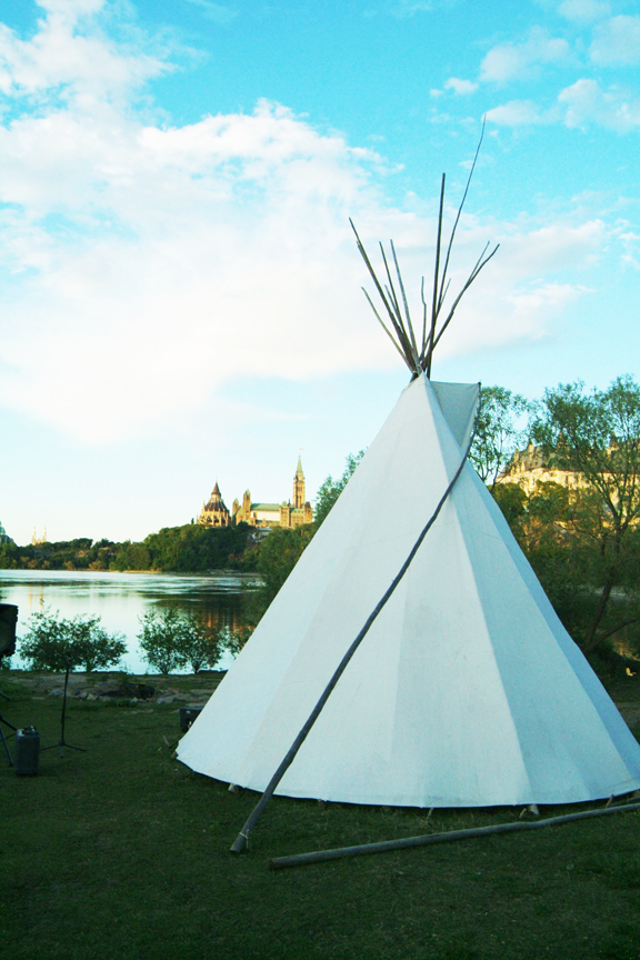 Teepee on grass in front of river and view of Parliament Buildings
